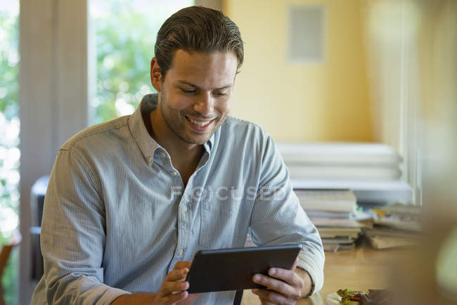 Man smiling and using digital tablet indoors. — Stock Photo