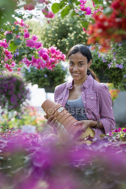Jeune femme portant une pile de pots à la pépinière de fleurs . — Photo de stock
