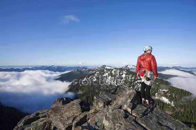 Bergsteiger steht mit Seil und Schutz auf Gipfel. — Stockfoto
