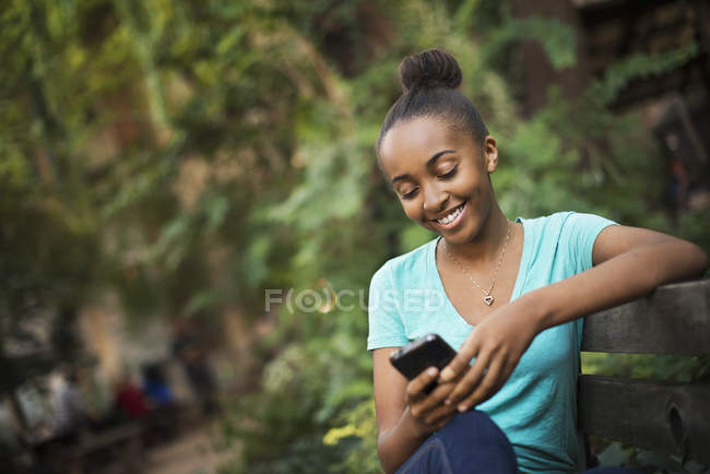 Teenage girl sitting on bench in park and using smartphone. — Stock Photo