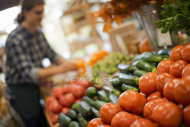 Young man arranging display of fresh produce on farm stand with tomatoes and cucumbers. — Stock Photo
