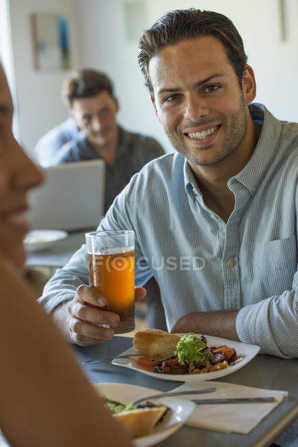Man smiling and looking in camera at cafe table with glass of beer. — Stock Photo