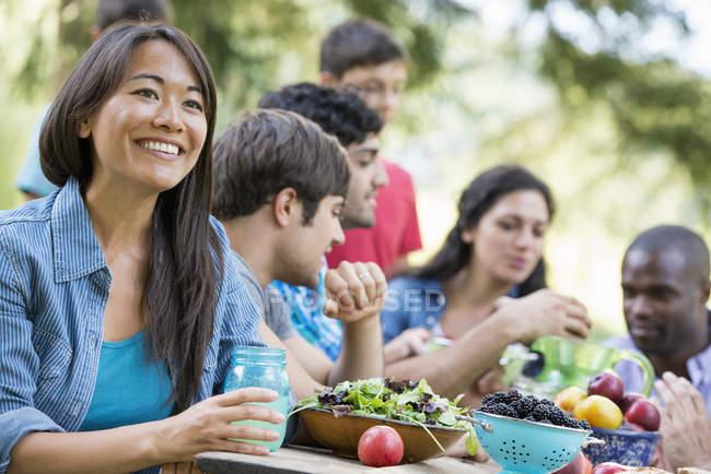 Femme tenant un verre avec des adultes et des enfants autour de la table à la fête dans le jardin . — Photo de stock