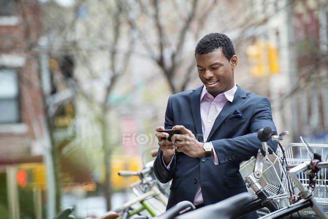 Giovane in tuta blu controllo smartphone nel parco biciclette . — Foto stock