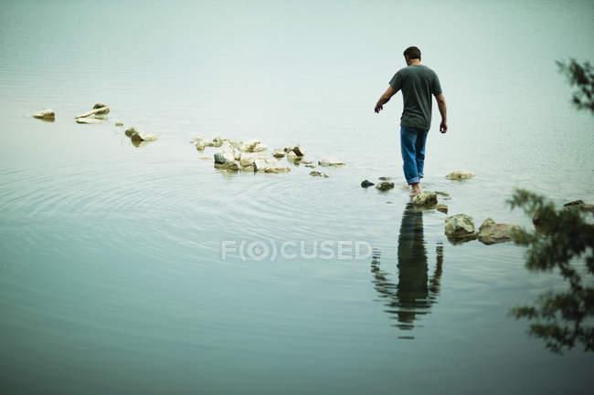 Homem andando descalço pisando pedras longe da costa do lago. — Fotografia de Stock