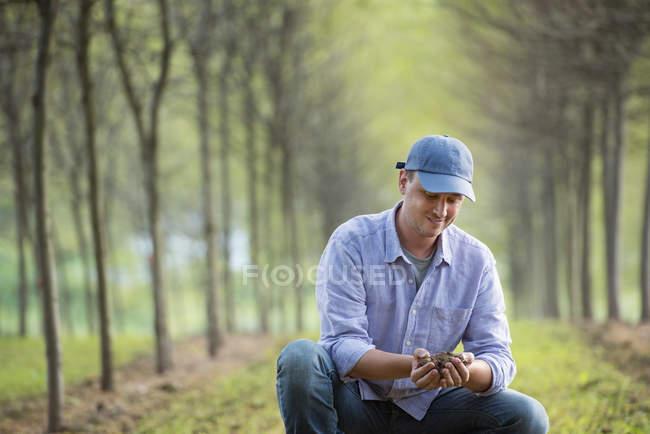 Mann mit Mütze hockt in Park mit Baumreihen und untersucht eine Handvoll Erde. — Stockfoto