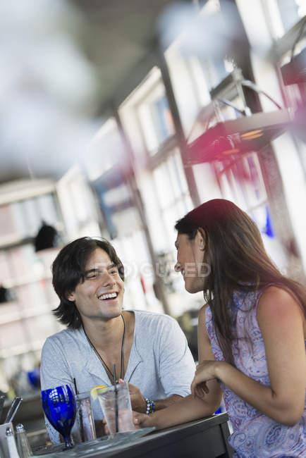 Jeune couple assis à la table servie à l'intérieur du café . — Photo de stock