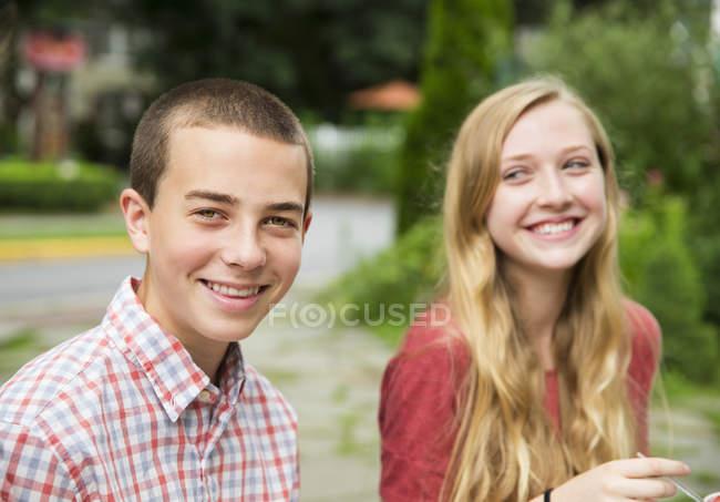 Ragazzo e ragazza che si siede fianco a fianco e che ride. — Foto stock