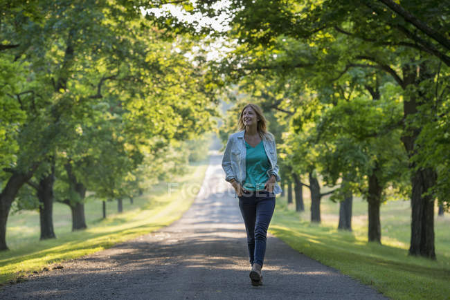 Mujer caminando por el camino del campo en el soleado parque . - foto de stock