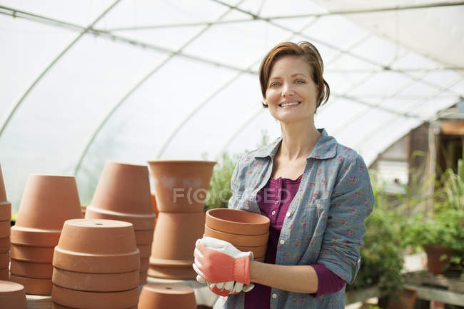 Woman wearing working gloves carrying terracotta plant pots in greenhouse. — Stock Photo