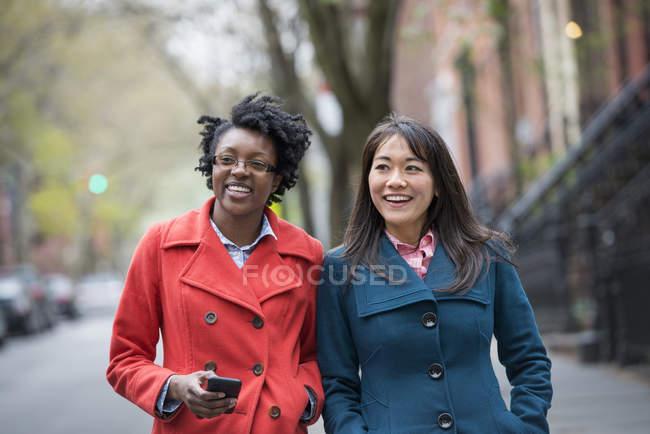 Двох жінок, що йдуть пліч-о-пліч на міській вулиці. — стокове фото