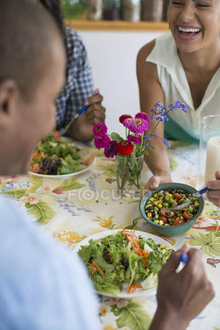 Woman laughing and sharing salad with friends in country kitchen interior. — Stock Photo