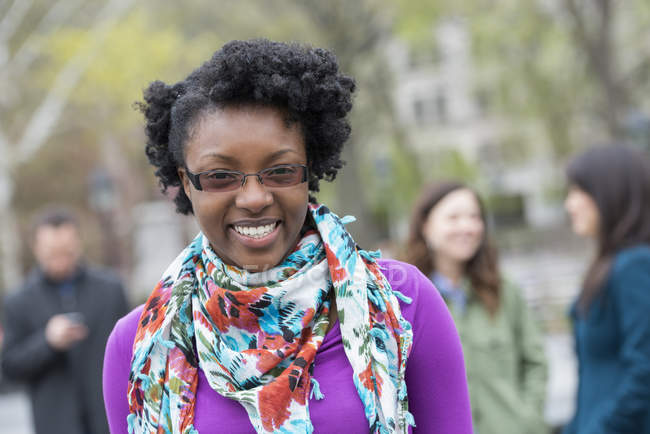 Young woman with floral scarf smiling and looking in camera with people in background. — Stock Photo