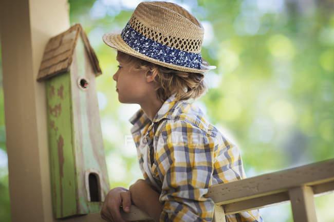 Блондин в шляпе, опирающийся на крыльцо с коробкой от жуков . — стоковое фото