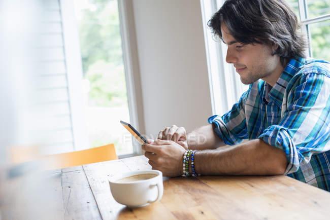 Giovane uomo che utilizza tablet digitale mentre seduto in un caffè con una tazza di caffè . — Foto stock