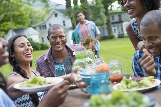 Young friends sharing plates with food at picnic table in countryside garden. — Stock Photo