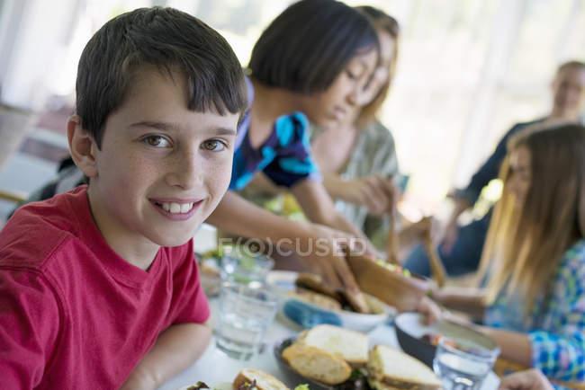 Préadolescents garçon souriant et regardant à huis clos avec les enfants à table — Photo de stock