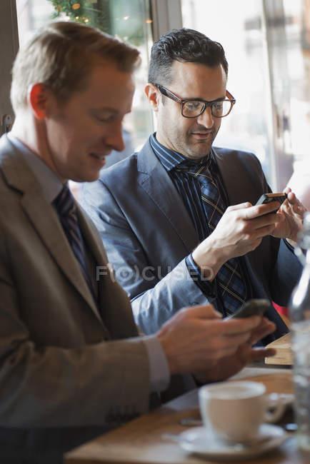 Empresários, sentado à mesa de café e verificação de telefones móveis — Fotografia de Stock