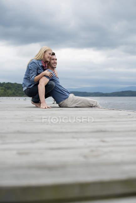 Uomo e donna seduti insieme e abbracciati sul molo vicino al lago . — Foto stock