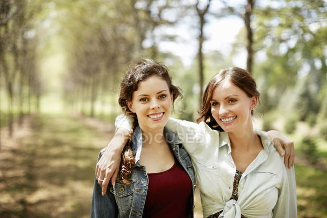 Female friends smiling and embracing on country road. — Stock Photo