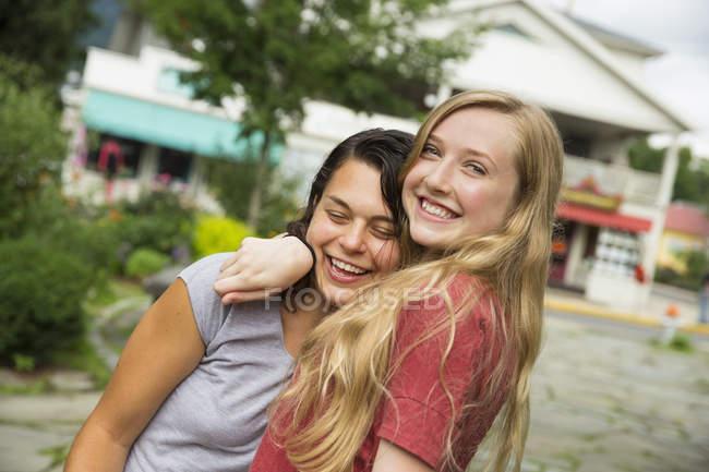 Ragazze adolescenti che abbraccia e che sorride sulla strada. — Foto stock