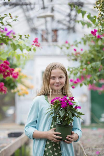 Pre-adolescente con flores en maceta en el vivero orgánico y mirando en cámara - foto de stock