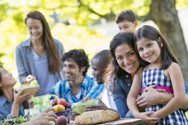 Woman hugging elementary age girl and looking in camera at outdoor party in garden. — Stock Photo