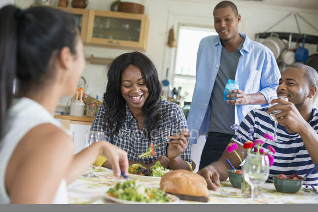 Group of friends laughing and sharing dinner in country kitchen interior. — Stock Photo