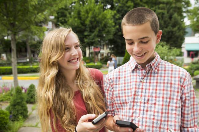 Ragazzo e ragazza che sorride e che tiene smartphone sulla strada. — Foto stock