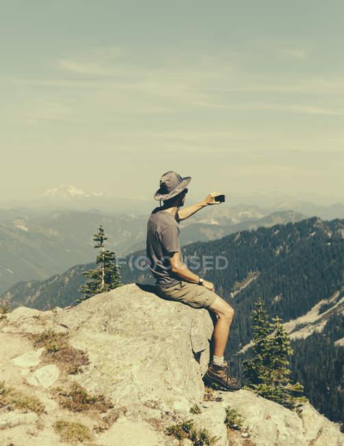 Männliche Wanderer sitzen auf Felsen und halten ihr Smartphone auf dem Gipfel des Überraschungsberges, Mount Bäcker National Forest, Washington, USA. — Stockfoto