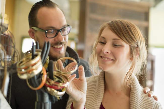 Paar betrachtet antiken Schmuck auf Schaufensterpuppe Hand. — Stockfoto