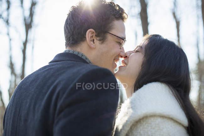 Casal jovem beijando e rindo na floresta no inverno . — Fotografia de Stock
