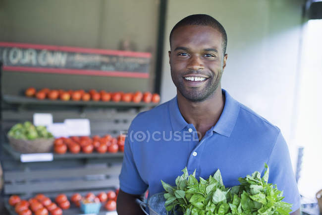 Man carrying green vegetables in organic farm store. — Stock Photo