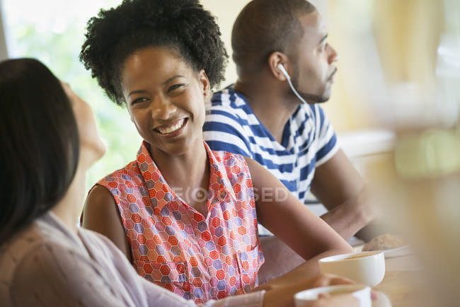 Women talking in coffee shop with man wearing earphones in background. — Stock Photo