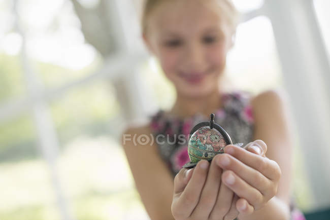 Close-up of small globe in cupped hands of pre-adolescent girl . — Stock Photo