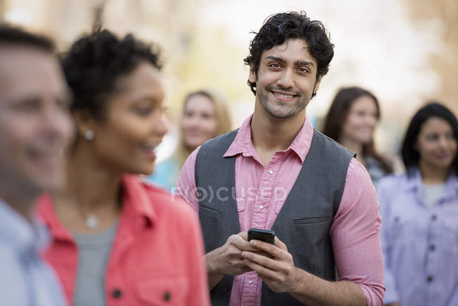 Young man holding mobile phone among group of men and women. — Stock Photo