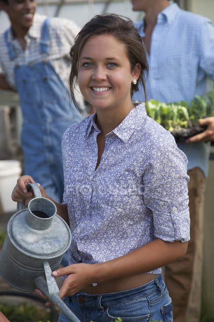 Young woman holding watering can with young men talking in greenhouse. — Stock Photo