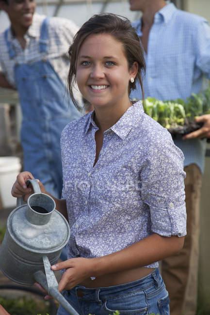 Mujer joven con riego puede con hombres jóvenes hablando en invernadero - foto de stock