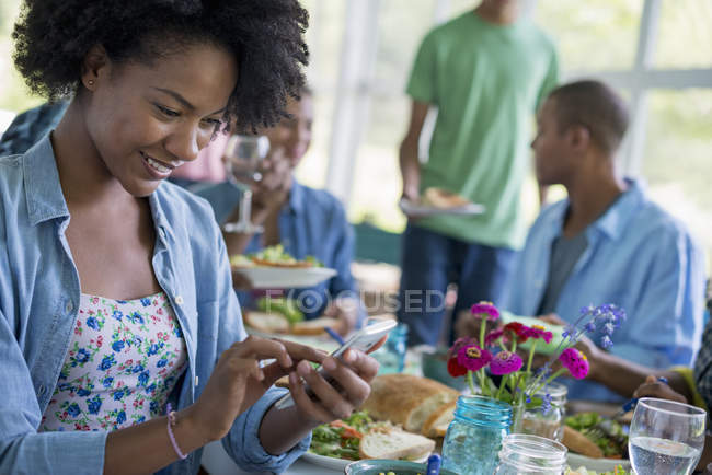 Woman using smartphone and smiling while dinner with friends in country house interior. — Stock Photo
