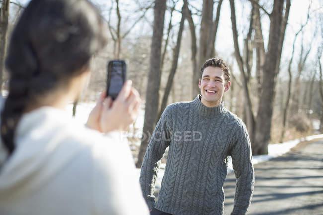 Женщина принимая фотография молодой человек с смартфон в зимний лес — стоковое фото
