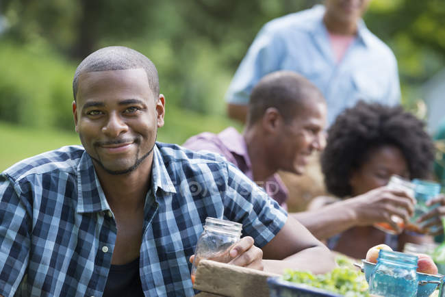 Man with glass smiling in camera with friends at picnic table in countryside garden. — Stock Photo