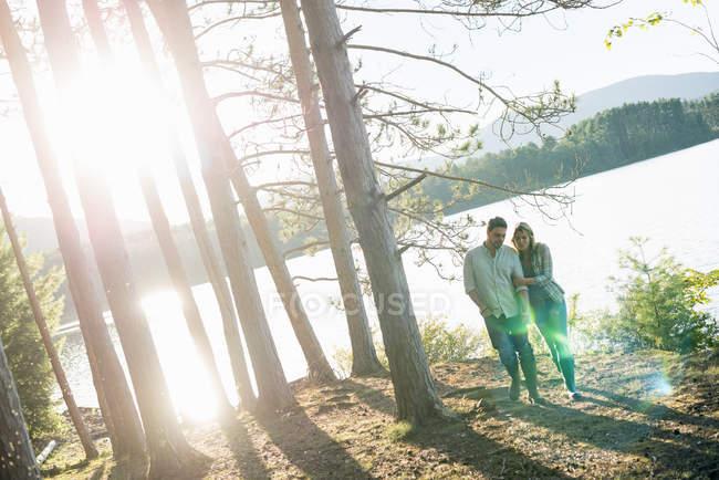 Couple marchant main dans la main dans la forêt sur la rive du lac forestier . — Photo de stock