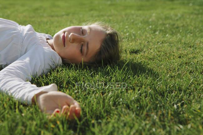Елементарний вік дівчини, відпочиваючи на зеленій траві з закритими очима — стокове фото