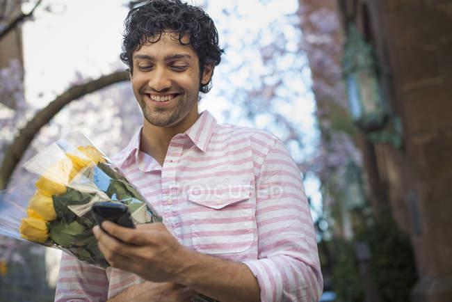 Молодой человек держит букет желтых роз и использует смартфон . — стоковое фото