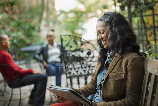 Donna che utilizza tablet digitale nel parco con persone che parlano in sedia in background . — Foto stock
