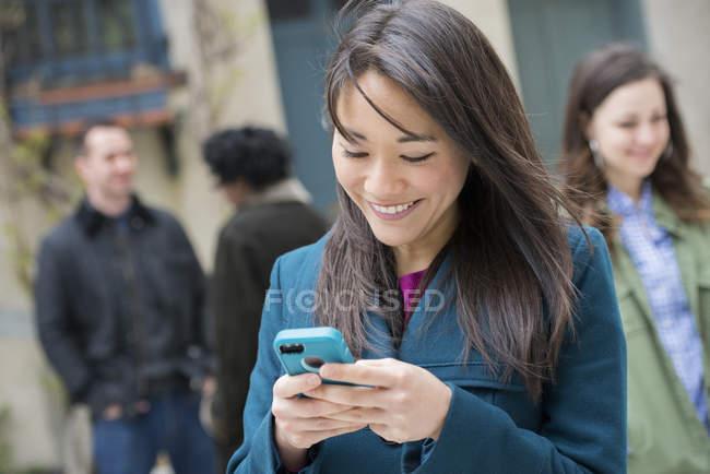 Mulher verificando turquesa smartphone entre as pessoas na rua da cidade . — Fotografia de Stock