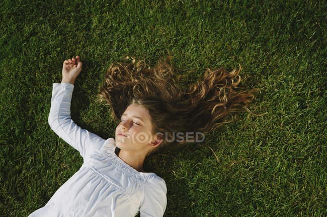 Niña de edad elemental descansando sobre hierba verde con los ojos cerrados - foto de stock