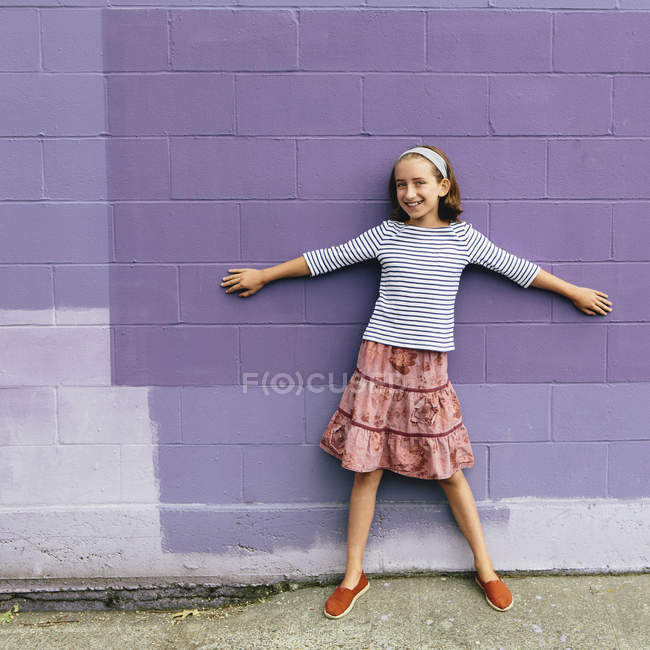 Pre-adolescent girl standing by purple wall with arms outstretched. — Stock Photo