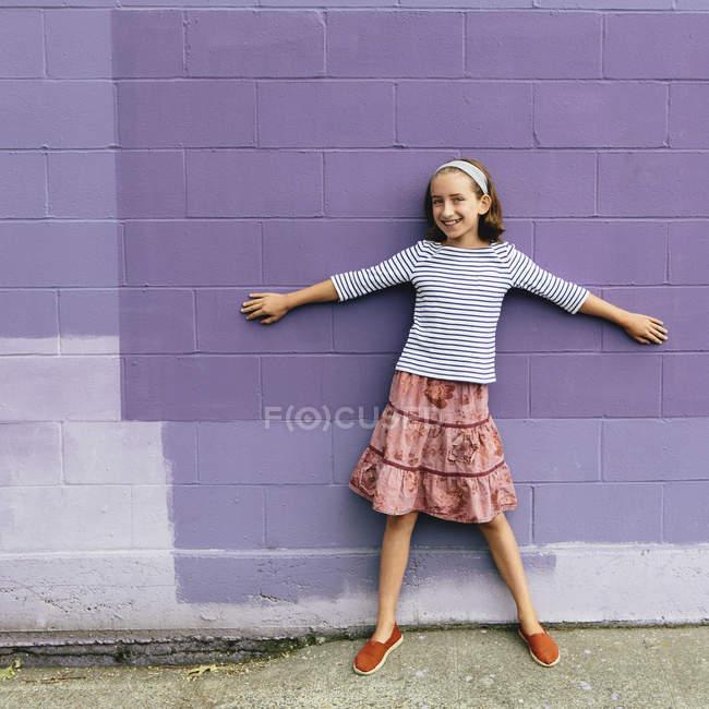 Pre adolescente por pared púrpura de pie con los brazos extendidos - foto de stock