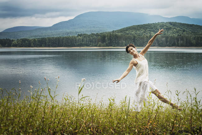 Woman dancing in open air along lake shore near Woodstock, New York State, USA — Stock Photo
